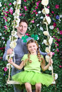 Smiling father and little girl with shamrock on head on swing in garden next to verdant fence Royalty Free Stock Photography