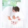 Smiling father putting his newborn baby in crib young a white round Stock Image