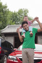 Smiling father with son on his shoulders looking at camera outdoors Stock Photography
