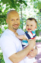 Smiling father and son outdoors in park age of months Stock Image