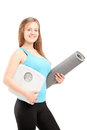 A smiling female athlete holding a weight scale and mat isolated on white background Stock Photo