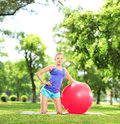 Smiling female athlete with a pilates ball in park posing Royalty Free Stock Photos
