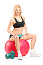 A smiling female athlete resting on a fitness ball Stock Image