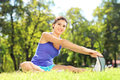 Smiling female athlete stretching in a park sitting on an excercising mat and Royalty Free Stock Photos