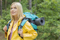 Smiling female backpacker in raincoat looking away at forest Royalty Free Stock Photos