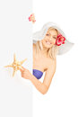 Smiling female in bikini holding a starfish and posing behind a blank panel isolated on white background Royalty Free Stock Photography