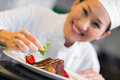 Smiling female chef garnishing food closeup of a in the kitchen Royalty Free Stock Image