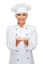 Smiling female chef holding something on hands cooking advertisement and food concept cook or baker palm of Stock Photography