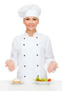 Smiling female chef with salad and cake on plates cooking food concept cook or baker Royalty Free Stock Image