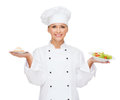 Smiling female chef with salad and cake on plates cooking food concept cook or baker Royalty Free Stock Photography