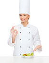 Smiling female chef with salad on plate cooking and food concept and ok sign Stock Photos