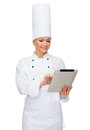 Smiling female chef with tablet pc computer cooking technology and food concept Royalty Free Stock Photos