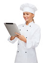 Smiling female chef with tablet pc computer cooking technology and food concept cook or baker Stock Images