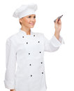 Smiling female chef writing something on air cooking new techology advertisement and food concept cook or baker with marker Royalty Free Stock Photo