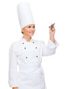 Smiling female chef writing something on air cooking new techology advertisement and food concept with marker virtual screen Stock Photo