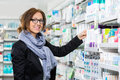 Smiling female consumer choosing product in portrait of pharmacy Stock Image