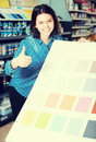 Smiling female customer examining color scheme variants in paint Royalty Free Stock Photo