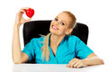 Smiling female doctor or nurse sitting behind the desk and holding heart toy Royalty Free Stock Photo