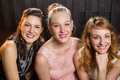 Smiling female friends sitting together in sofa at bar Royalty Free Stock Photo