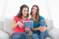 Smiling female friends using digital tablet in the living room portrait of two young at home Stock Images