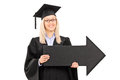 Smiling female in graduation gown holding a big black arrow poin Stock Image