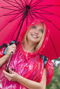 Smiling female hiker in red raincoat holding umbrella Royalty Free Stock Photos