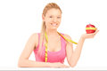 Smiling female holding an apple wrapped with measuring tape Royalty Free Stock Photos