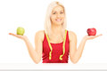 Smiling female holding two apples and measuring tape around her isolated on white background Stock Images