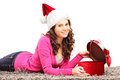Smiling female lying down and opening gift Stock Images