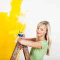 Smiling female painting yellow interior white wall in color of new house Royalty Free Stock Photos