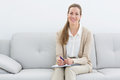 Smiling female psychologist sitting on sofa in her office Stock Image