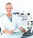 Smiling female researcher sitting at a laboratory Stock Photography
