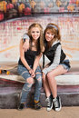 Smiling female skateboarders two sitting together Royalty Free Stock Photo