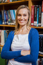 Smiling female student with arms crossed in the library Royalty Free Stock Photo
