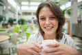 Smiling female student drinking coffee in the cafeteria close up portrait of a Royalty Free Stock Photography