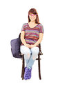 Smiling female student with school bag sitting on a chair wooden isolated white background Royalty Free Stock Images