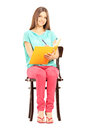 Smiling female student sitting on a chair and writing notes isolated white background Stock Image