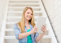 Smiling female student with tablet pc computer education and technology concept sitting on staircase Stock Photo