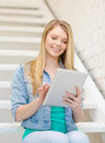 Smiling female student with tablet pc computer education and technology concept sitting on staircase Stock Photography