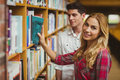 Smiling female student taking book Royalty Free Stock Photo