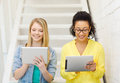 Smiling female students with tablet pc computer education and technology concept sitting on staircase Royalty Free Stock Photos