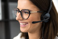 Smiling female support operator in headset closeup portrait of a Stock Photos