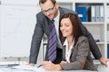 Smiling female team leader manageress or businesswoman showing paperwork to her male business colleague or partner as they discuss Royalty Free Stock Photos