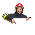 Smiling fireman in red helmet pointing at the blank banner standing behind placard and head and shoulders studio shot isolated on Stock Images