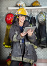 Smiling firewoman holding digital tablet at fire in uniform looking away while station Royalty Free Stock Photo