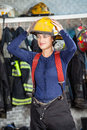 Smiling firewoman wearing helmet at fire station looking away while Royalty Free Stock Image
