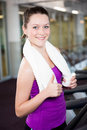 Smiling fit woman with towel around her neck standing in the gym Royalty Free Stock Images