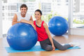 Smiling fit young couple with exercise ball at gym portrait of a sitting a bright Royalty Free Stock Photography