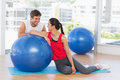 Smiling fit young couple with exercise ball at gym portrait of a sitting a bright Royalty Free Stock Images