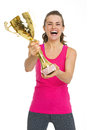Smiling fitness woman showing gold trophy cup Royalty Free Stock Photo